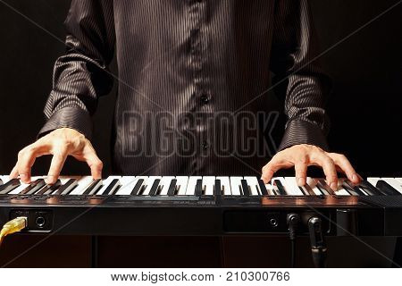 Musician playing the synthesizer on a black background