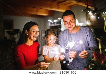 Beautiful young family with little daughter with sparklers at Christmas time at home.