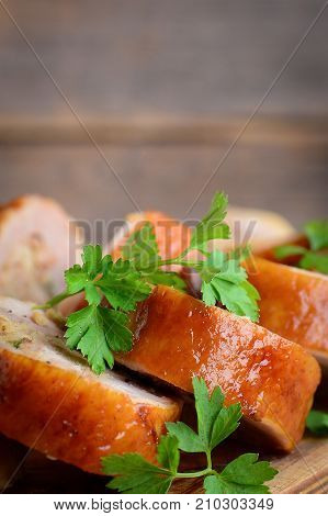 Chicken breast with filling. Baked chicken rolls, fresh parsley on a wooden board. How to make stuffed chicken breast with stuffing idea. Vertical photo. Closeup