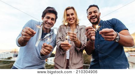 Group of friends enjoying rooftop party with sparklers. Millennial group of friends holding sparklers on rooftop at sunset. poster