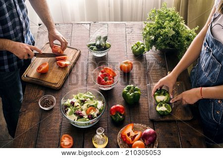 Married couple cooking together dinner vegetables salad in home kitchen top view. Healthy lifestyle concept