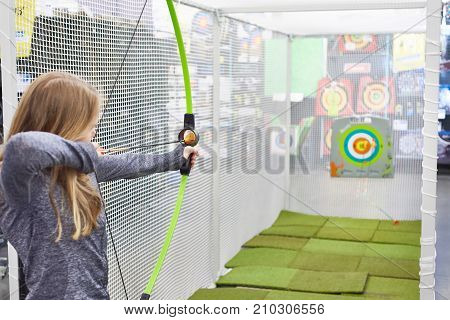 girl shoots a bow in a children's shooting range