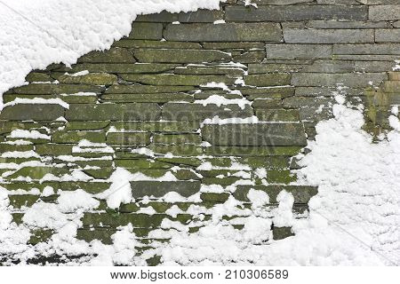 Snow-covered stone wall. Stone wall covered with snow in low temperatures.