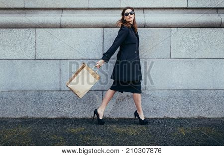 Full length of young woman walking along the city street with shopping bags. Stylish female shopper outdoors looking at camera. Woman out for a shopping in city.