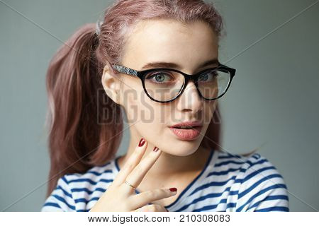 Close up portrait of amazing gorgeous young European woman with two pinkish ponytails looking at camera with lips slightly parted demonstrating her stylish make up and red manicured nails at camera