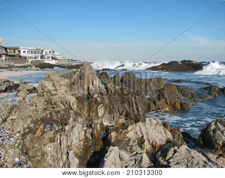 ROUGH WINTER SEA IN THE BACK GROUND, WITH HUGE BOULDERS IN THE FORE GROUND
