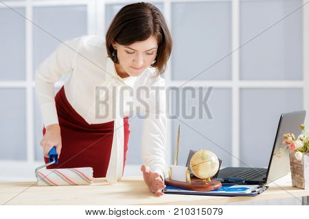 attractive business woman changing activity. woman paints a table with a platen and sheds office items off the table