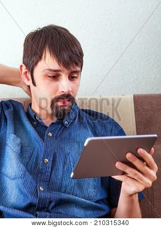 Man with Tablet Computer on the Sofa at the Home