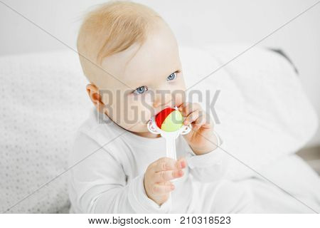 Baby with blond hair and big light eyes takes rattle in mouth with serious face expression dressed in white crawler sits