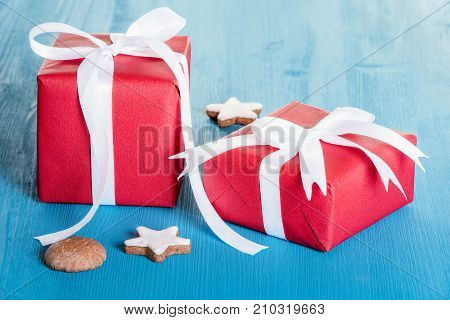 Red wrapped gift boxes - Gift boxes wrapped with red paper and tied with white ribbon and bow on a blue wooden table.