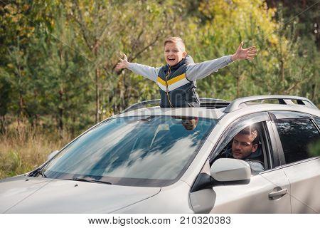 Boy Standing In Car Sunroof