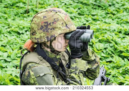Portrait of armed woman with camouflage. Young female soldier observe with binoculars. Child soldier with gun in war green goutweed background. Military army people concept