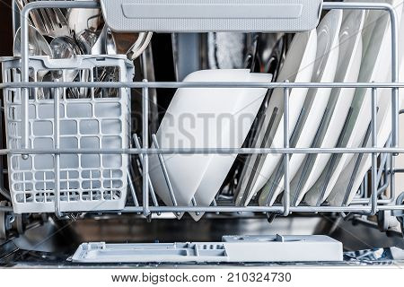 Open Dishwasher With Clean Glass And Dishes.