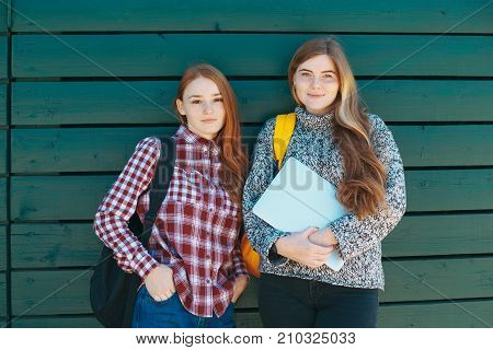 Two college students or high school girls on green wooden background smiling with backpacks and laptop in hands. Students Youth Friendship Concept. Teenagers Young Team Together Cheerful.