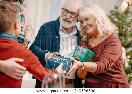 happy grandparents presenting beautiful gifts to grandson