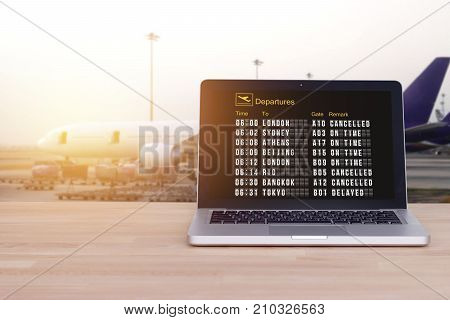 Technology for comfortable travel tourist traveler concept : Flight status on notebook laptop with airport and blur airplane background film effect. Check in online. Check flight status online.