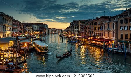 Venice, Italy - May 17, 2017: Grand Canal with gondola at night in Venice. Grand Canal is one of the major water-traffic corridors in Venice.
