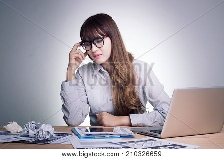 Feeling sick stressed and tired. Stress young business woman of working age is working on a wooden table at her working place in office feel under pressure. Asian woman model in her 30s