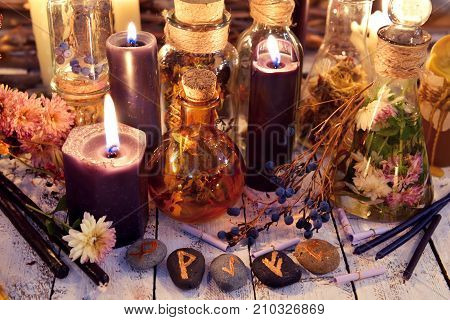 Magic runes, black candles, flowers and berries on witch table in candle light. Occult, esoteric, divination and wicca concept. Alternative medicine and Halloween vintage background