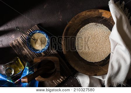 Wooden bowl of sesame seeds and olive oil horizontal
