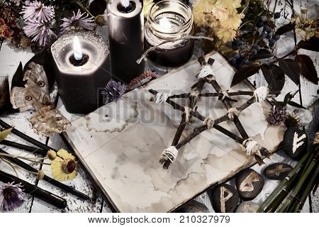 Open book with old empty pages, pentagram and black candles on witch table, toned image. Occult, esoteric, divination and wicca concept. Alternative medicine and Halloween vintage background