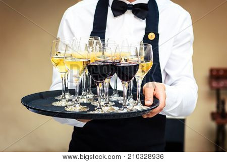 Professional Waiter In Black Uniform Serving Red And White Wine.
