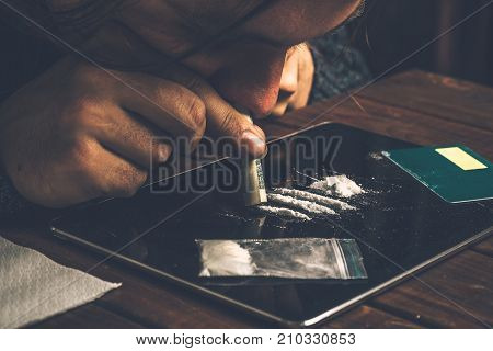 Junkie snorting cocaine powder with rolled dollar banknote. Narcotics and drug abuse concept, toned