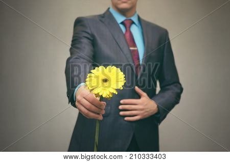 Gentle Man in suit gives yellow gerbera flower to someone. Meeting. Date. Rendezvous. Valentine day. poster