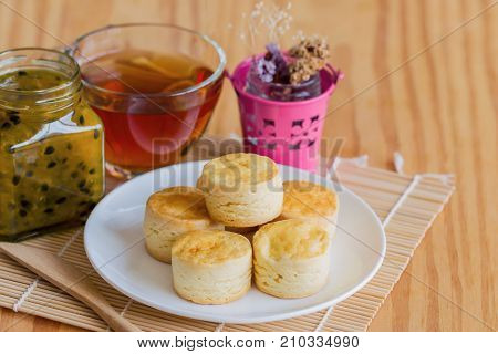 Homemade delicious plain scones serve with passion fruit jam and tea on wood table copy space for background or wallpaper. Scones is traditional English pastry for afternoon tea or coffee break. Scones and jam ready to served.