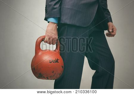 Debt. Debentures. Business man holding in his hands kettlebell with DEBT inscription isolated on grey background. poster