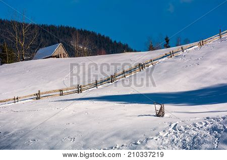 Woodshed Above The Snowy Hillside With Fence