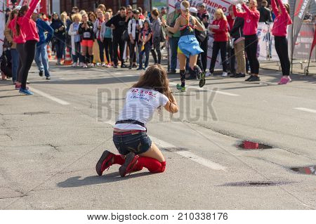 DNEPR UKRAINE - SEPTEMBER 24 2017:Female amateur photographer sitting on a street and making cool shot during
