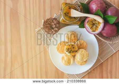 Homemade delicious scones with homemade passion fruit jam in top view flat lay with copy space for background or wallpaper. Scones is traditional English pastry for serve with afternoon tea or coffee. Scones and passion fruit jam on table.