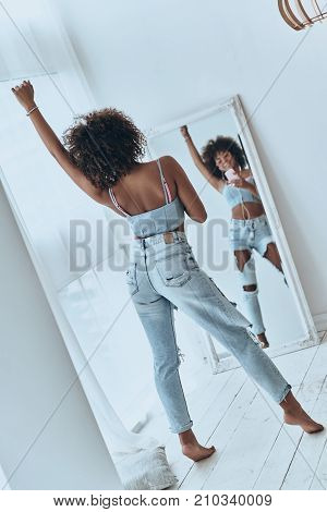 She is a superstar. Full length rear view of beautiful young African woman listening music and smiling while taking selfie at home
