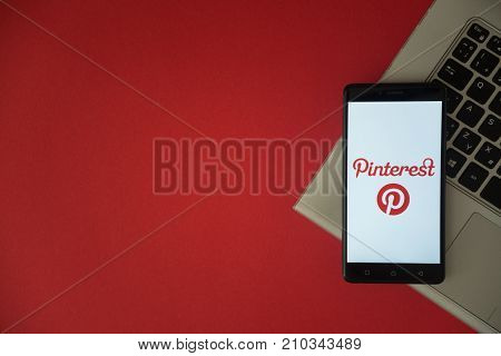 London, United Kingdom, October 23, 2017: Pinterest logo on smartphone screen placed on laptop keyboard. Empty place to write information with red background.
