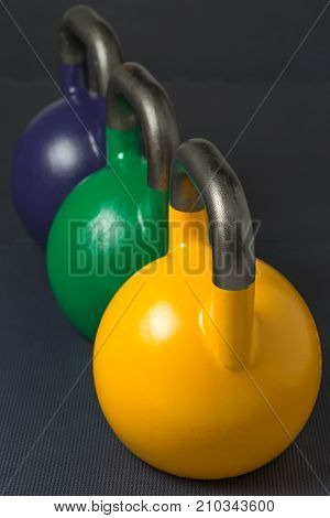 Yellow, green and dark purple competition kettlebells lined up in a row on a gym floor. Yellow competition kettlebells weigh 16kg. Green competition kettlebells weigh 24kg. Dark purple competition kettlebells weigh 20kg.