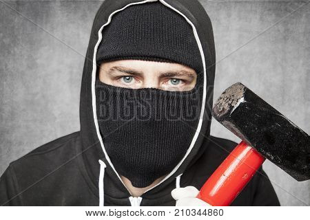 Close-up On A Masked Stranger, Hammer In A Hand