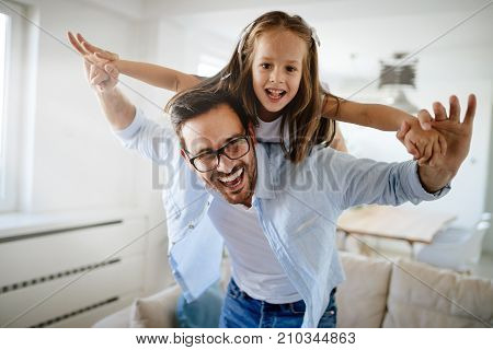 Portrait of father and daughter playing at home together