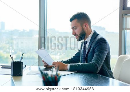 Profile view of concentrated young white collar worker wrapped up in paperwork while sitting at desk, interior of modern office with panoramic windows on background