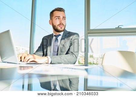 Portrait of handsome young white collar worker looking away pensively while distracted from work on promising project, interior of modern office with panoramic windows on background