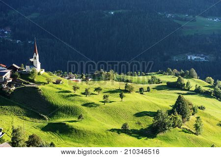 Chapel and sheep on the meadow. Bell tower trees shrubs and hilly green grassland. Heiliger Antoniuse church and houses in the evening light. Pitburger See Taxegg Salzburg Austria Europe