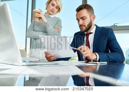 Beautiful young white collar worker with paper cup of coffee in hand studying financial figures with her male colleague while having working meeting at open plan office