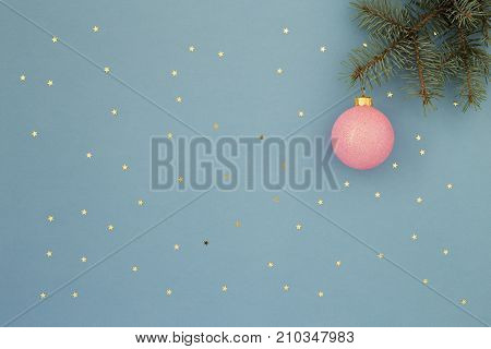 Pink Christmas ball and spruce. Blue holiday background with gold stars sequins. Minimal New Year greeting card. Shining Night sky at Christmas time