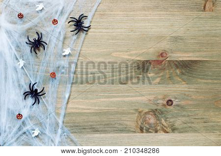 Halloween background with spider web spiders and smiling jack decorations as symbols of Halloween on the wooden background. Halloween holiday concept. Halloween festive background. Halloween still life. Halloween background