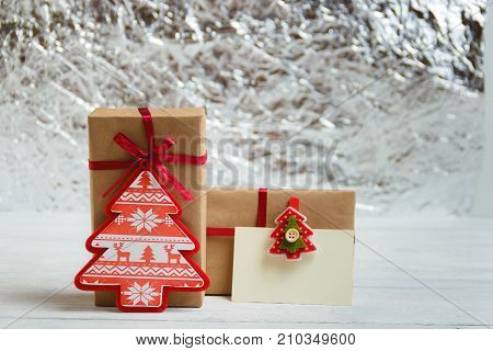 Vintage gift box package with blank gift tag on white wooden background.