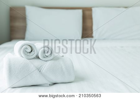 Roll Of White Towel On The Bed Table In Luxury Modern Hotel Room