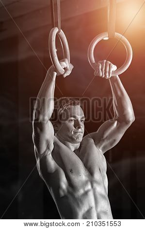 Muscular young shirtless man doing intense workout on gymnastics rings. Strength or callistenics workout. Fitness, sports concept.