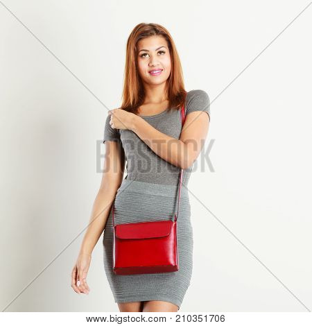 Female fashion. Girl mixed race in fashionable gray outfit with red leather bag handbag. Studio shot