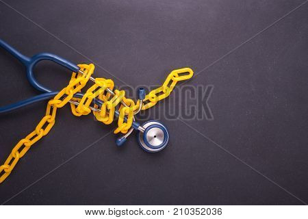 Yellow Chain Locked Around The Doctor Stethoscope On Black Stone Board. Stop, Control Or Avoid Healt