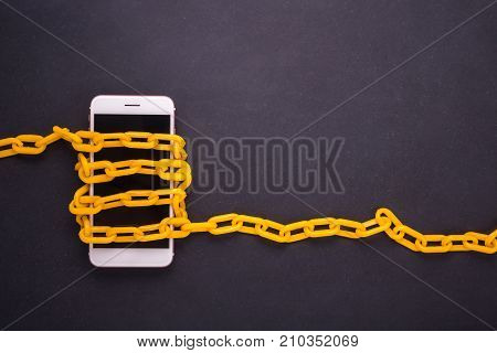 Yellow Chain Locked Around The Smartphone On Black Stone Board. Stop, Control Or Avoid Using Smartph
